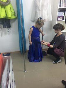 """На фото хозяйка ателье """"Новый образ"""" в г.Краснодар примеряет детское платье на девочке"""