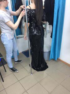 """На фото хозяйка ателье """"Новый образ"""" в Краснодаре примеряет на девушке вечернее черное платье"""