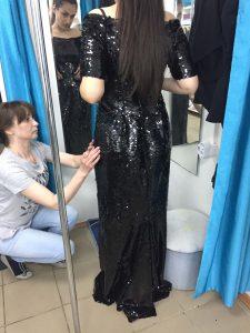 На фото девушка примеряет черное вечернее платье