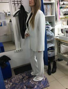 На фото девушка примеряет женский костюм