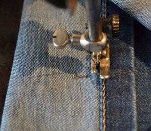 На фото проводят машинную строчку по окружности джинсов